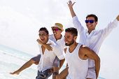 picture of bachelor party  - Four male friends at the beach - JPG