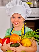stock photo of pinafore  - Child in cooking hat holding vegetable at kitchen - JPG