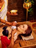 picture of panchakarma  - Indian woman taking ayurvedic massage with pouch of rice - JPG