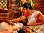 image of ayurveda  - Indian woman does facial mask at ayurveda spa - JPG