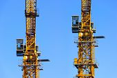 stock photo of heavy equipment operator  - Two construction yellow tower cranes with operator cabins isolated on blue sky background - JPG