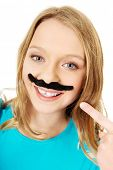 stock photo of moustache  - Happy teenage woman with a moustache - JPG