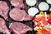 foto of pork chop  - Nice thick pork chops on the grill with onions and an iron skillet of vegetables on the side - JPG