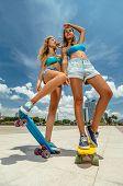 stock photo of skateboarding  - Portrait of beautiful skateboarding women on skateboards at summer park - JPG
