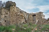 foto of fallen  - Entire view of ruined house with fallen walls against blue sky - JPG