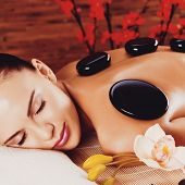 pic of stone-therapy  - Adult woman relaxing in spa salon with hot stones on back - JPG