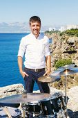 picture of drum-kit  - Young handsome guy in a white shirt drummer sitting behind the drum kit outdoors and unseat him the sea and beautiful sky - JPG