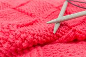 stock photo of knitting  - red knitted fabric and two knitting needled - JPG