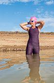 picture of dam  - Athletic female triathlete entering a dam in preparation for her swim - JPG