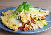 picture of grating  - Tasty Omelet with Tomatoes Leek and Grated Cheese on Grey Plate closeup on Wooden background - JPG