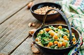 stock photo of chickpea  - chickpeas and spinach curry on a dark wood background - JPG