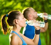picture of cold drink  - Man and woman drinking water from bottle after fitness sport exercise - JPG