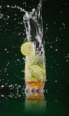 stock photo of mojito  - Fresh mojito drink with ice cubes and splashes on black background - JPG