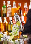 pic of mojito  - Mojito cocktail drink on bar counter with barman holding shaker on background - JPG