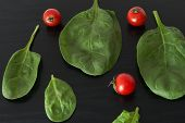 image of black-cherry  - Still life with cherry tomatoes and spinach on black background - JPG
