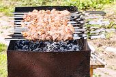 stock photo of brazier  - skewers with shish kebabs on brazier with hot charcoal on backyard - JPG
