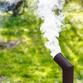pic of chimney  - White smoke from the chimney of a samovar on backyard - JPG