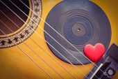 stock photo of heart sounds  - An acoustic guitar with a vinyl record and a red love heart - JPG