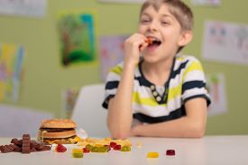 picture of gummy bear  - Smiling child eating gummy bears at school