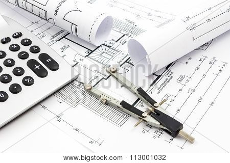 Architectural drawings of a house with compass and calculator