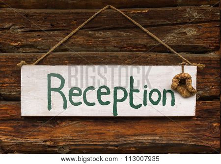 Reception sign on wooden background at a traditional wooden chalet in the mountains