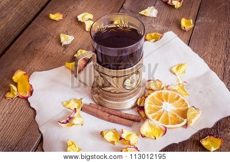 Cup Of Tea In Coaster, Dried Oranges, Dried Rose Petals On Wooden Background