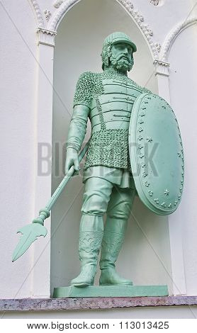 Sculpture of a medieval knight with shield and spear on the building.