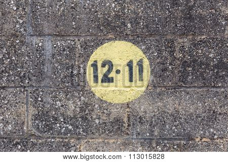 Black Numbers In A Yellow Circle Painted On Dark Brickwork Wall In The Outdoors
