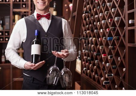 Skillful young sommelier is serving a customer