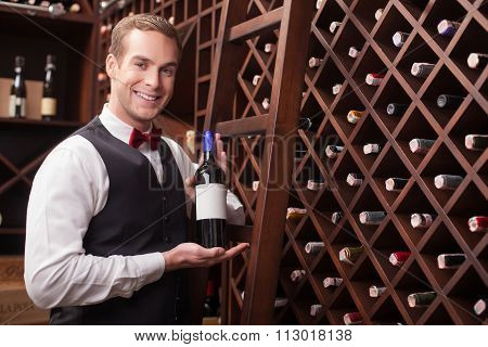 Attractive young sommelier is showing elegant drink
