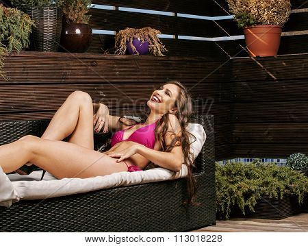 beauty young real woman after spa in bikini and robe at hotel resort, on terrace enjoying warm sun