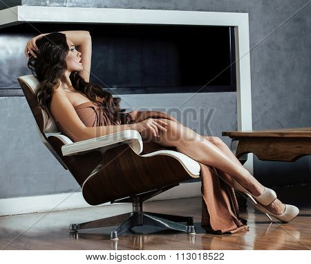 beauty young brunette woman sitting near fireplace at home, winter warm evening in interior, waiting