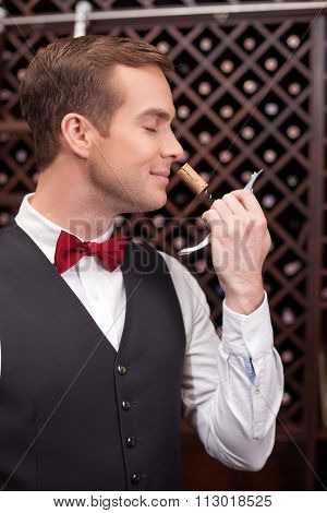 Attractive male wine waiter with a bottle-screw