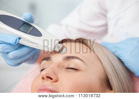 Skillful female beautician is treating her patient