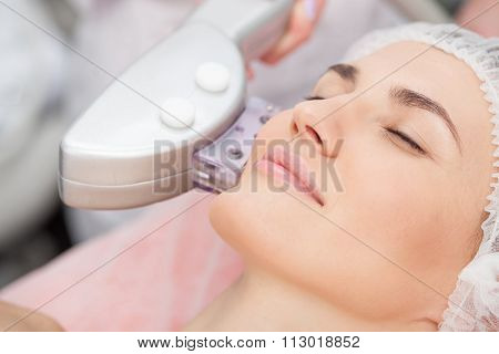 Skillful young cosmetologist is treating female face