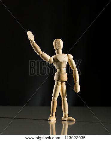 Human wood manikin is waving against dark background