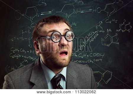 Bizarre professor in glasses thinking over chemical formulas on blackboard