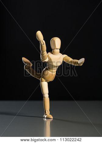 Human wood manikin dancing against dark background