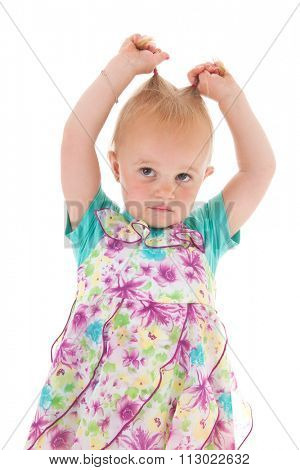 Portrait toddler girl pulling the pigtails in summer dress isolated over white background