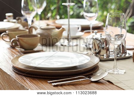 ethnic outdoor table setting on solid wood table