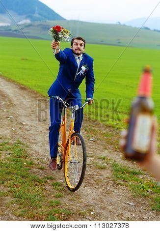 drunken groom on a bike holding a wedding bouquet is running after a bride with a beer bottle.