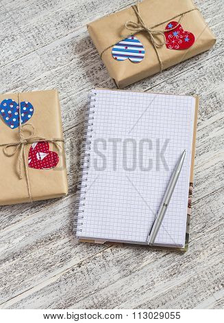 Open  Clean Notepad,  Homemade Valentine's Day Gifts In Kraft Paper, Paper Hearts On White Wooden Ta