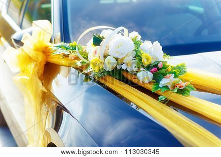 Luxury wedding car decorated with flowers. White flower and ribbons.