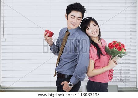 Attractive Couple Holding A Gift And Flowers