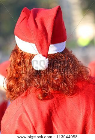 Long Red Hair With A Red Cap And The Costume Of Santa Claus