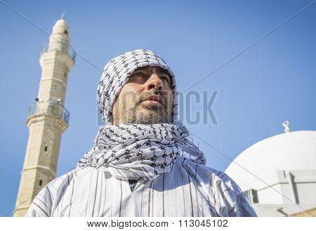 Arab Man Wearing Keffiyeh Below A Mosque