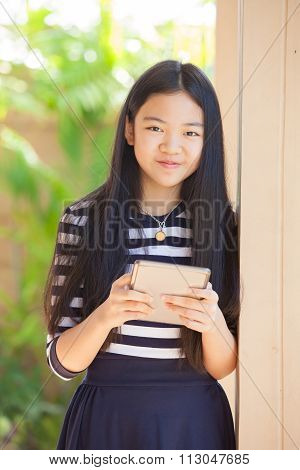 Twelve Years Old Asian Kid Standing With Happiness Smiling Face And Tablet Computer In Hand Use For