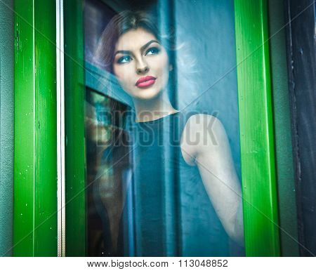 Beautiful sexy woman posing in a green painted window frame, shot through window. Sexy gorgeous girl