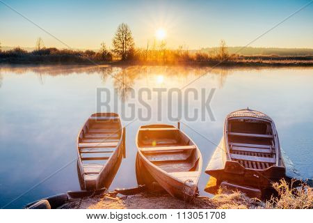 River and old wooden rowing fishing boat at beautiful sunrise