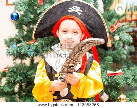 Little Boy Child Dressed As Pirate For Halloween  On Background Of Christmas Tree. Kid In Carnival C